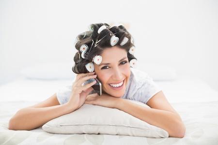 hair rollers: Morena sonriente en los rodillos del pelo que mienten en la cama que hace una llamada de tel�fono en el dormitorio en casa