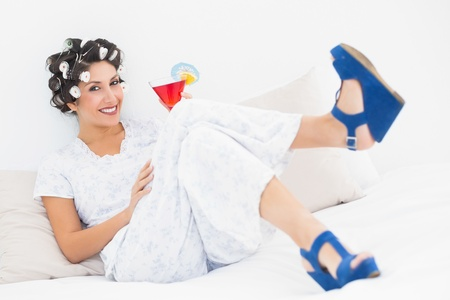 Brunette in hair curlers and wedge shoes holding a cocktail in bedroom at home