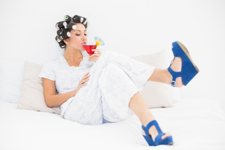 Brunette in hair rollers and wedge shoes drinking a cocktail in bedroom at home photo
