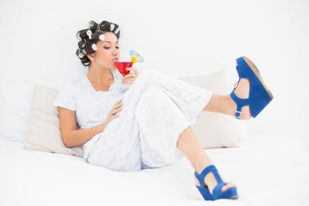hair rollers: Morena en rodillos de pelo y zapatos de cu�a bebiendo un c�ctel en el dormitorio en casa