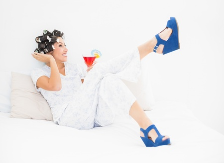 Brunette in hair rollers and wedge shoes holding a cocktail in bedroom at home photo