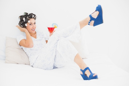 Brunette in hair rollers and wedge shoes holding a cocktail looking at camera in bedroom at home