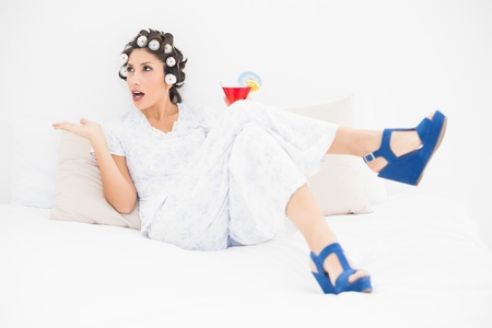 Brunette in hair rollers and wedge shoes holding a cocktail gesturing on bed in bedroom at home photo