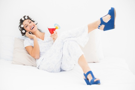 Brunette in hair rollers and wedge shoes having a cocktail making a call on bed in bedroom at home photo
