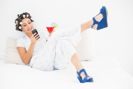 Brunette in hair rollers and wedge shoes having a cocktail sending a text on bed in bedroom at home photo