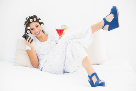hair rollers: Morena en rodillos de pelo y zapatos de cu�a con un c�ctel con smartphone en la cama en el dormitorio en casa Foto de archivo