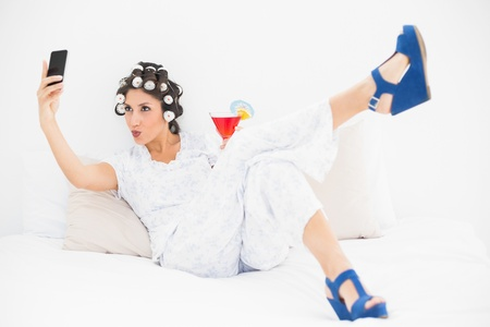 Brunette in hair rollers and wedge shoes having a cocktail taking a selfie in bedroom at home