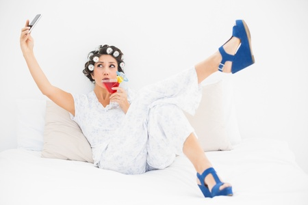 Brunette in hair rollers and wedge shoes drinking a cocktail taking a selfi in bedroom at home Stock Photo