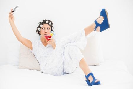 Brunette in Lockenwickler und Keil Schuhe trinken einen Cocktail unter einen Selfi im Schlafzimmer zu Hause