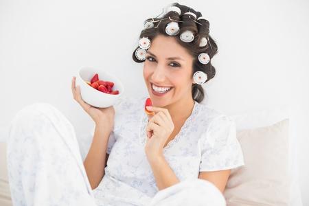 hair rollers: Alegre morena en rulos con un taz�n de fresas en casa en el dormitorio