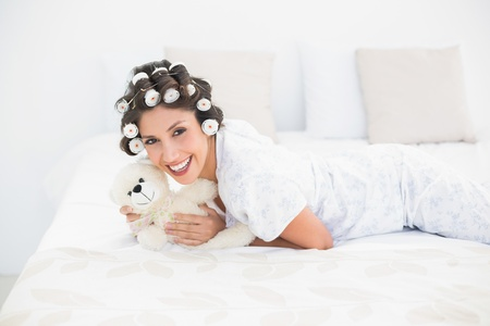 Pretty brunette in hair rollers cuddling her teddy on bed at home in bedroom
