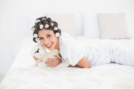 hair rollers: Pretty morena en rulos abrazo su peluche en la cama en su casa en el dormitorio