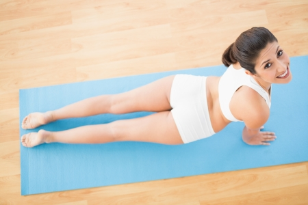 Fit woman stretching in cobra pose at home on wooden floor photo