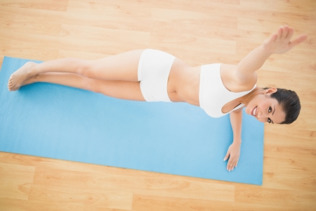 Fit woman doing a side plank and smiling at camera at home on wooden floor