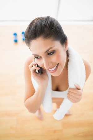 Fit woman on the phone taking a break at home in bright room photo
