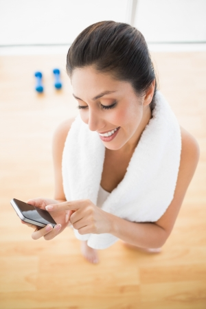 Fit woman using smartphone taking a break from workout at home in bright room photo
