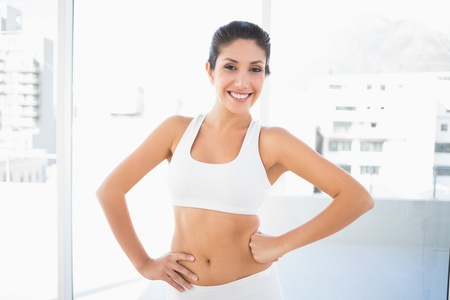 tied woman: Fit happy woman in sportswear with hands on hips at home in bright room