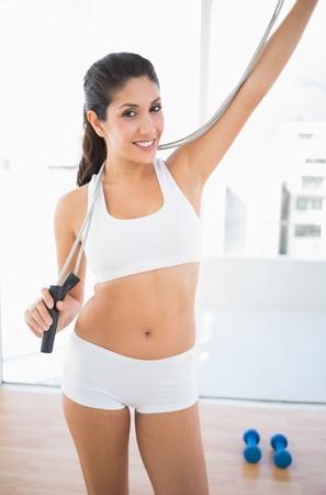 saltar la cuerda: Montar una mujer feliz en ropa deportiva de saltar la cuerda celebraci�n en casa en la habitaci�n luminosa Foto de archivo