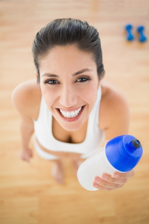 Fit smiling woman holding sports bottle  at home looking at camera Stock Photo - 21771315