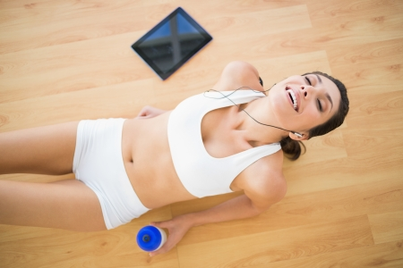 Fit smiling woman holding sports bottle resting  at home on parquet floor photo