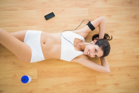 Fit happy woman doing sit ups listening to music at home on parquet floor photo
