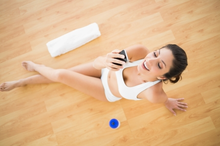 Fit happy woman sending a text during her workout at home on parquet floor photo