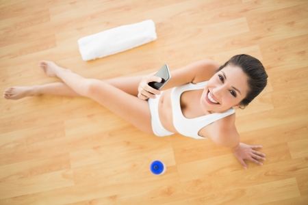 Fit happy woman sending a text during her workout looking at camera at home on parquet floor photo