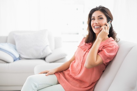 Happy brunette sitting on her sofa on the phone at home in the living room photo