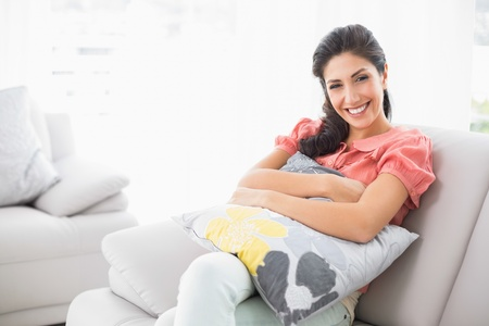 Happy brunette sitting on her sofa smiling at camera at home in the living room photo