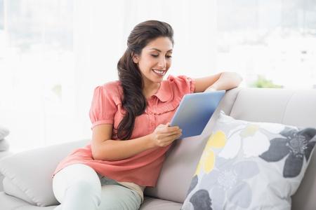 tied hair: Happy bruna seduta sul suo divano con tavoletta a casa in salotto