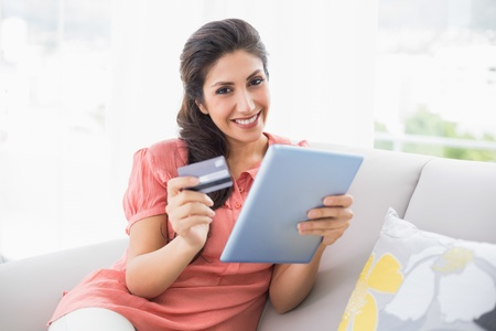 Smiling brunette sitting on her sofa using tablet to shop online at home in the living room photo