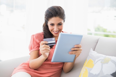 Happy brunette sitting on her sofa using tablet to shop online at home in the sitting room photo