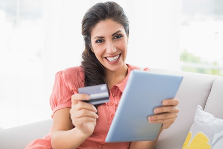Pretty brunette sitting on her sofa using tablet to shop online at home in the sitting room photo