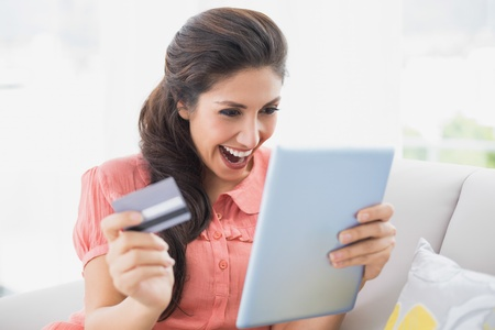 Ecstatic brunette sitting on her sofa using tablet to shop online at home in the sitting room photo