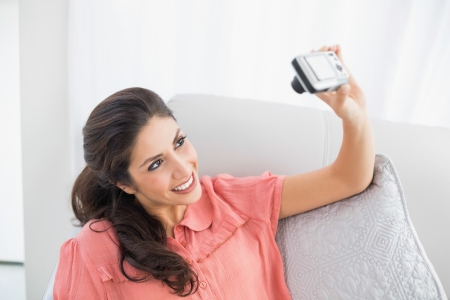 Brunette sitting on her sofa taking a picture of herself at home in the sitting room photo