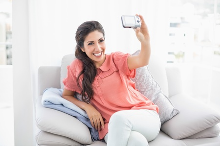 Pretty brunette sitting on her sofa taking a picture of herself at home in the sitting room photo