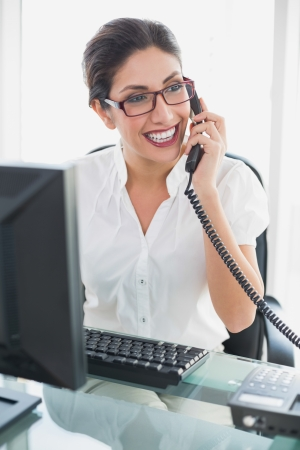 Happy businesswoman sitting at her desk talking on the phone in her office Stock Photo
