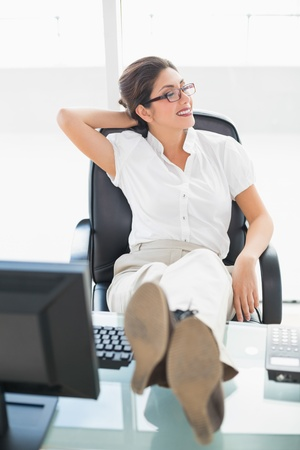 Relaxed businesswoman sitting at her desk with her feet up in her office photo