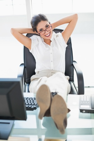 Relaxed businesswoman sitting at her desk with her feet up looking at camera in her office