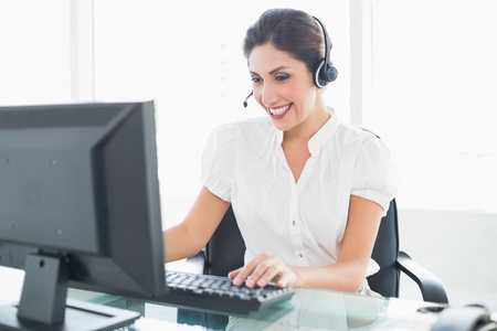 Cheerful call centre agent working at her desk on a call in her office