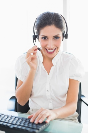 Smiling call centre agent working at her desk on a call in her office photo