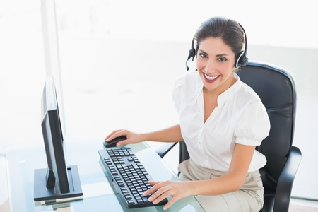 Happy call centre agent working on computer while on a call in her workplace photo