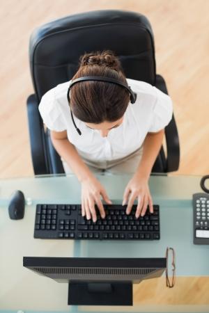 call center agent: Call center agent digitando durante una chiamata in suo luogo di lavoro