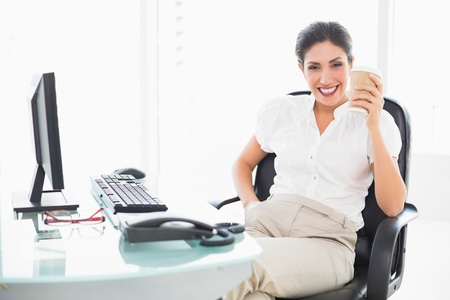 Happy businesswoman drinking a coffee at her desk in her workplace photo