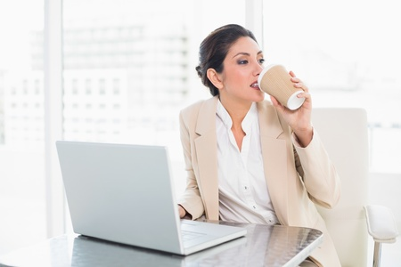 Stylish businesswoman drinking coffee while working on laptop at the office photo