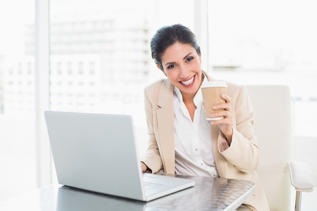 Happy businesswoman drinking coffee while working on laptop at the office photo