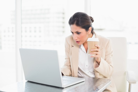Concentrating businesswoman drinking coffee while working on laptop at the office photo