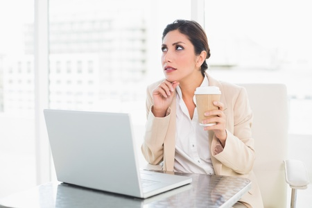 Thoughtful businesswoman drinking coffee while working on laptop at the office photo