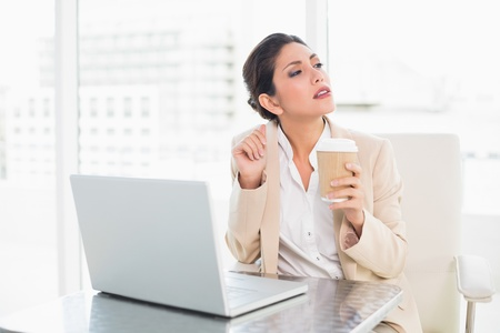 Thinking businesswoman drinking coffee while working on laptop at the office photo