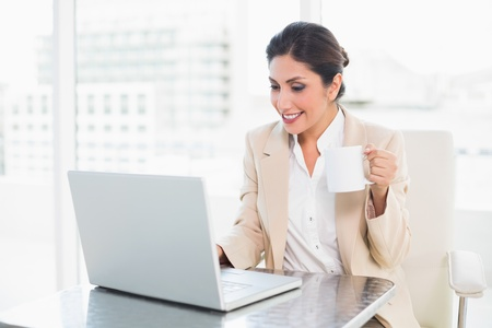 Cheerful businesswoman holding mug while working on laptop at the office photo
